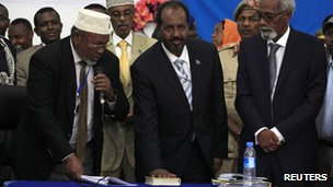President Hassan Sheikh Mohamud (c) with his hand on the Koran