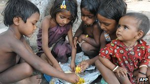 Children eating in a slum dwelling in India