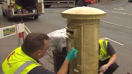 The post box being painted gold in Hay-on-Wye