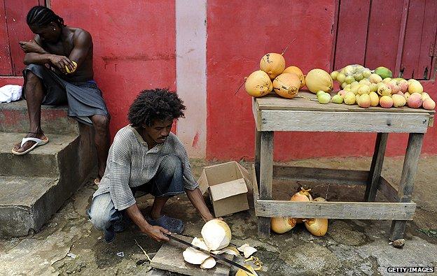 Carib tribesmen prepares coconuts