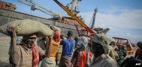 In a photograph released by the African Union-United Nations Information Support Team on 6 August 2012, dock workers load sacks of imported cement inside the seaport of Mogadishu, Somalia
