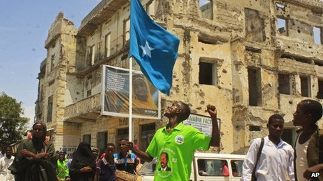 "A Somali man wearing T-shirts with a picture of Somalia""s new president Hassan Sheikh Mohamud march through the streets to show his support, in Mogadishu, Somalia, Tuesday, Sept. 11, 2012."