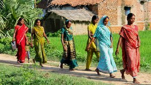 Village women walking past a hut.