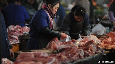 Vendors sell pork at a market in China