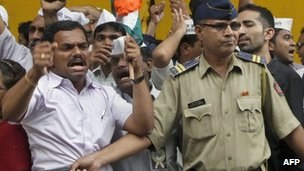 A policeman tries to stop activists of India Against Corruption protesting against the arrest of political cartoonist Aseem Trivedi, outside the jail where he is being held in Mumbai, 11 Sept 2012