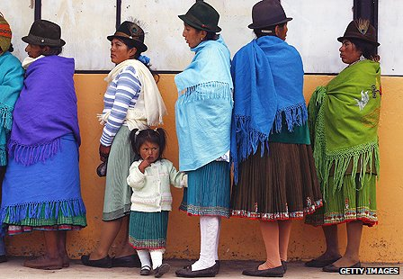 Native Ecuadoran women queue outside a polling station