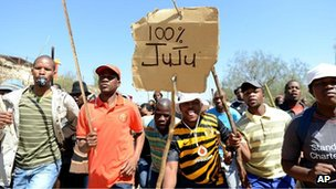 Striking mine workers listen to firebrand politician Julius Malema, nicknamed Juju, them at the Gold Fields mine, near Carletonville, west of Johannesburg, South Africa, on Tuesday