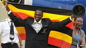 Ugandan Olympics marathon gold winner Stephen Kiprotich holds a flag on arrival to Entebbe International Airport on 15 August 2012