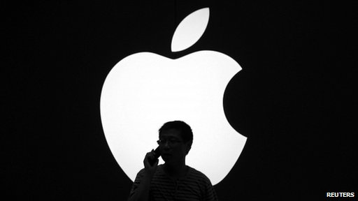Man uses iPhone in front of Apple logo