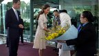 Prince William looks on as his wife Catherine receives flowers upon arrival at Changi International Airport in Singapore
