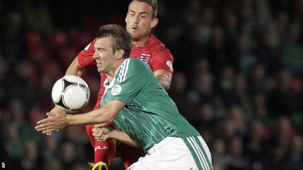 NI defender Gareth McAuley is challenged by Aurelien Joachim