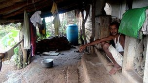 Man sits in his home that is a temporary hut