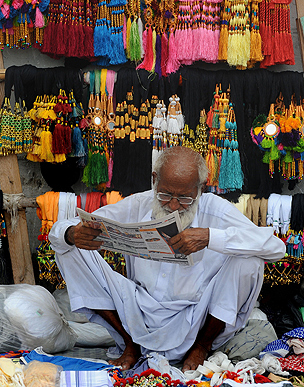 Vendor reads newspaper in Pakistan market