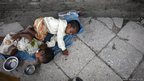 Children sleep by the side of the road
