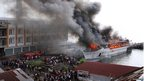 People watch as a passenger ship is engulfed in flames in Manado