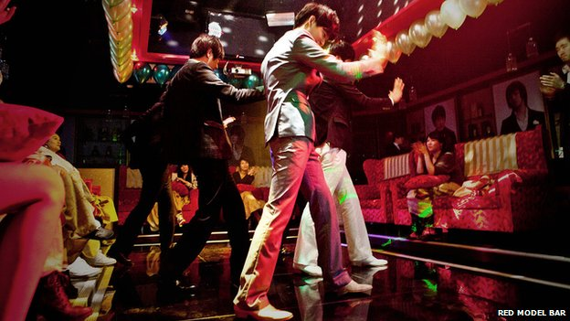 Male hosts dance at the Red Model Bar in Seoul, South Korea