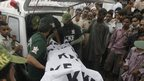Rescue workers loading a dead body into an ambulance in Karachi 12 September 2012