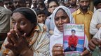 A woman holding a portrait of her son while waiting with others for news of the dead 12 September 2012