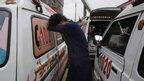 Man weeping beside ambulances near the garment factory in Karachi 12 September 2012