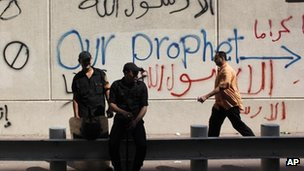 Egyptian soldiers stand guard in front of the US embassy, defaced by people protesting against an allegedly offensive film about the Prophet Muhammad, in Cairo, Egypt, on Wednesday