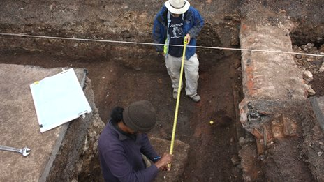 Archaeologists recording the grave