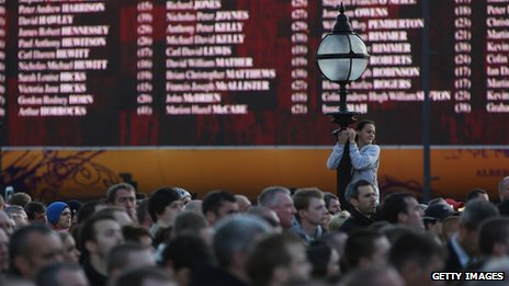 People gather before giant screen displaying names of the 96 victims