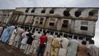 Onlookers outside the burnt hulk of the garment factory on Thursday