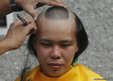 A female marine corps recruit has her head shaved