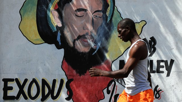 A man walks past a Bob Marley painting in Kingston, Jamaica
