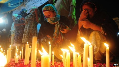 Relatives of fire victims light candles outside the Ali Enterprises garment factory in Karachi on September 13, 2012