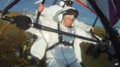 Russian President Vladimir Putin flies in a motorized hang glider alongside a Siberian white crane