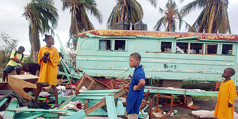 Children among debris of their storm-damaged school
