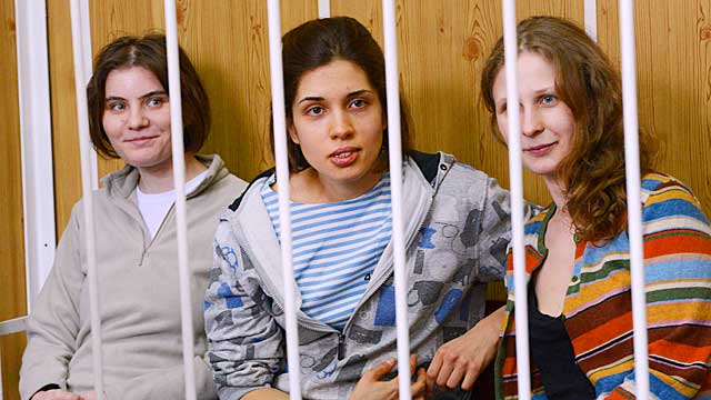 Pussy Riot members Nadezhda Tolokonnikova (C), Maria Alyokhina (R) and Yekaterina Samutsevich (L), sit behind bars during a court hearing in Moscow