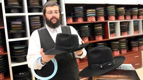 """Meir Rutner holds up a """"kneytsh"""" (""""pinch"""") fedora"""