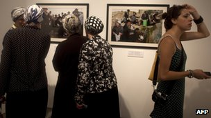 Ultra-Orthodox women and a secular woman look at exhibition photographs