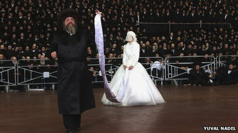 Still from video showing rabbi dancing with the bride who is held on the end of a sash