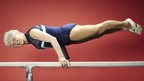 World's oldest gymnast balances on a bar.