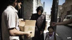 Woman receives food parcel in Aleppo