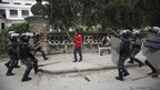 Nepalese riot police surround a student participating in a torch rally organized by various student unions in Kathmandu