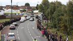 Students from Raynes Park line Burlington Road as the horse-drawn carriage carrying Tia Sharp's coffin passes by