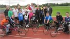 Alex (with stick, centre) tries out wheelchair racing!