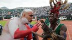 A Tunisian football fan (L) and a Sierra Leonean fan (R) hold up two fingers in a stadium in Freetown, Sierra Leone, during a match - Saturday 8 September 2012