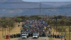 Miners walk to South Africas Lonmin platinum mine on Monday