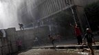 Protesters chant and throw missiles as they are sprayed with a police water cannon in Cairo, 14 September 2012