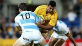 Australia's Kurtley Beale is tackled by two Argentinians