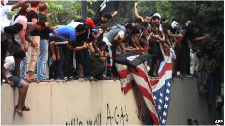 Protesters tear down a US flag at the US embassy in Cairo, Egypt (11 Sept 2012)