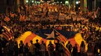 Hundreds of people march through Barcelona holding placards and waving Catalonia's flag in the annual Catalan independence rally on 11 September 2012
