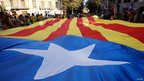 "A giant ""Estelada"" flag is held up by protesters during Catalonia's independence rally in Barcelona on 11 September 2012"