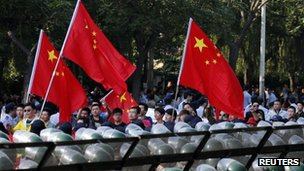 Protesters wave Chinese flags while marching outside Japanese embassy during a protest in Beijing