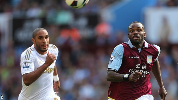 Swansea defender Ashley Williams challenges Darren Bent of Aston Villa